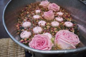Zinkwanne gefüllt mit Schwimmkerzen, Rosen und Blüten