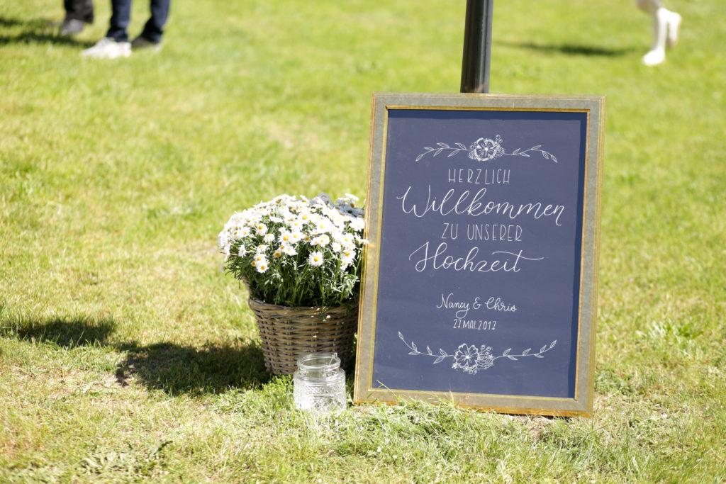 Belettertes Willkommenschild für die Hochzeit auf schwarzem Karton in einem goldenen Rahmen.